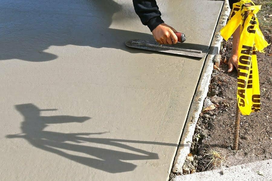"""a concrete laborer trowels wet """"mud"""" concrete on a sidewalk repair project."""