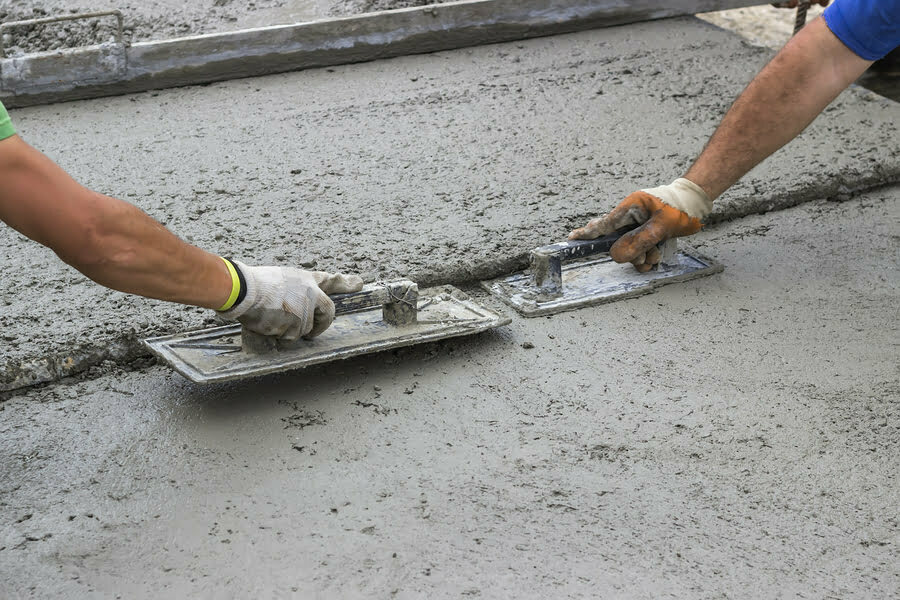 leveling concrete with trowels mason hands spreading poured concrete